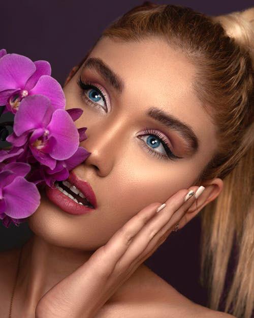 visage bronzé, maquillage jour cils contour des œils et lèvres rouge.