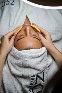 Soins du visage lingette avec les mains dans une serviette grise