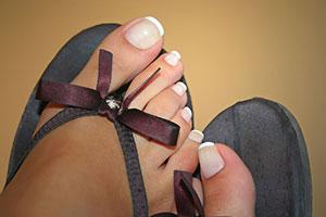 ongle de pieds dans les claquettes à noeud