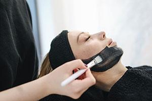 Soins visage passer le pinceau avec le produit sur les joues